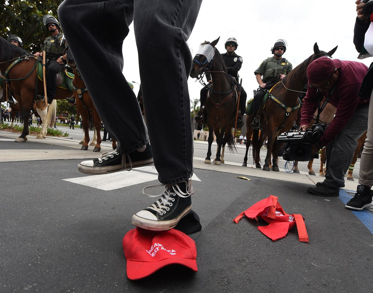 A Trump protester stomps on a Make America Great Again hat.