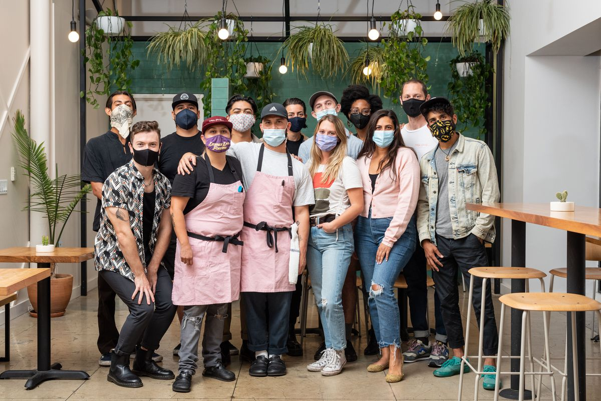 A group of employees in a mask stand posing for a photo in front of their restaurant.