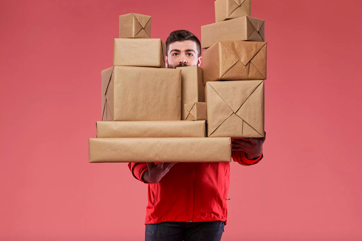 A man in a red sweatshirt and black pants is holding several paper bag-wrapped packages against a pink background