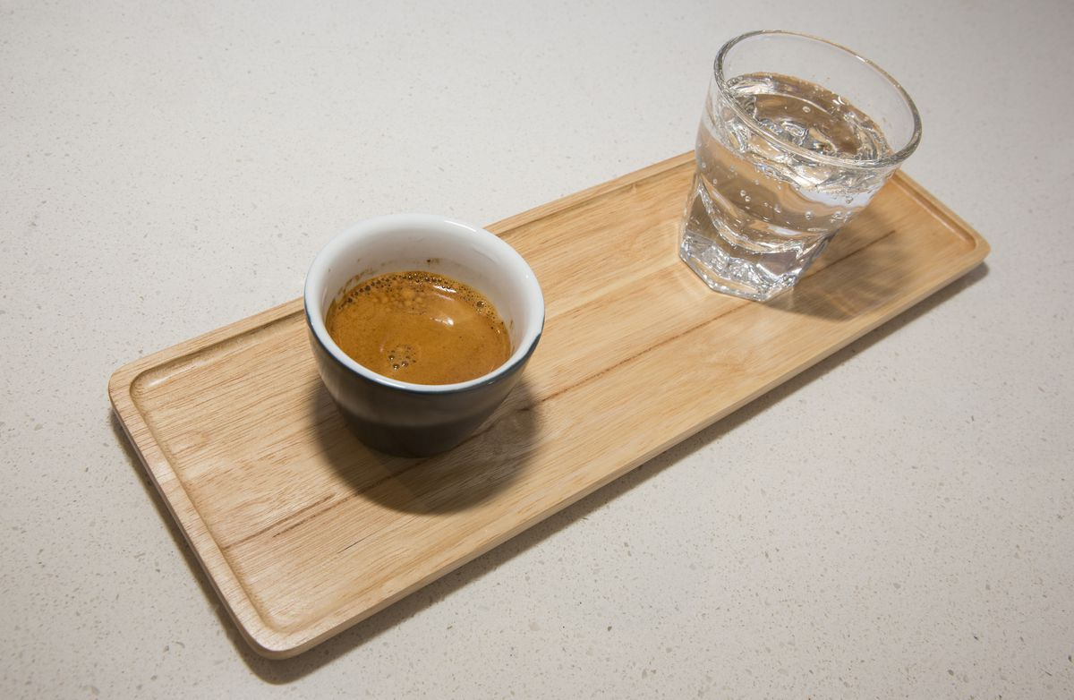 An espresso and glass of sparkling water on a wooden tray.