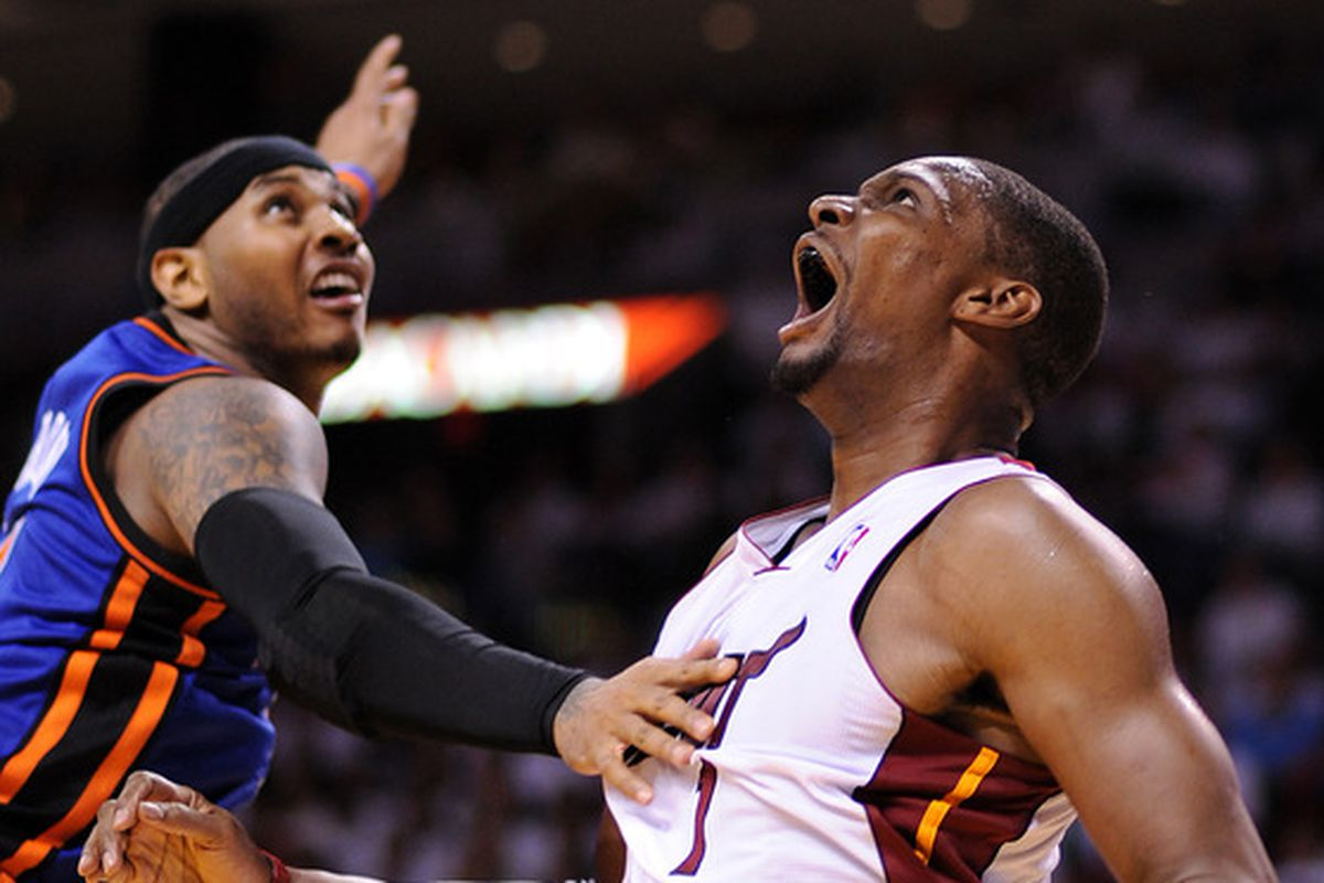 Chris Bosh and Carmelo Anthony fight for a rebound.