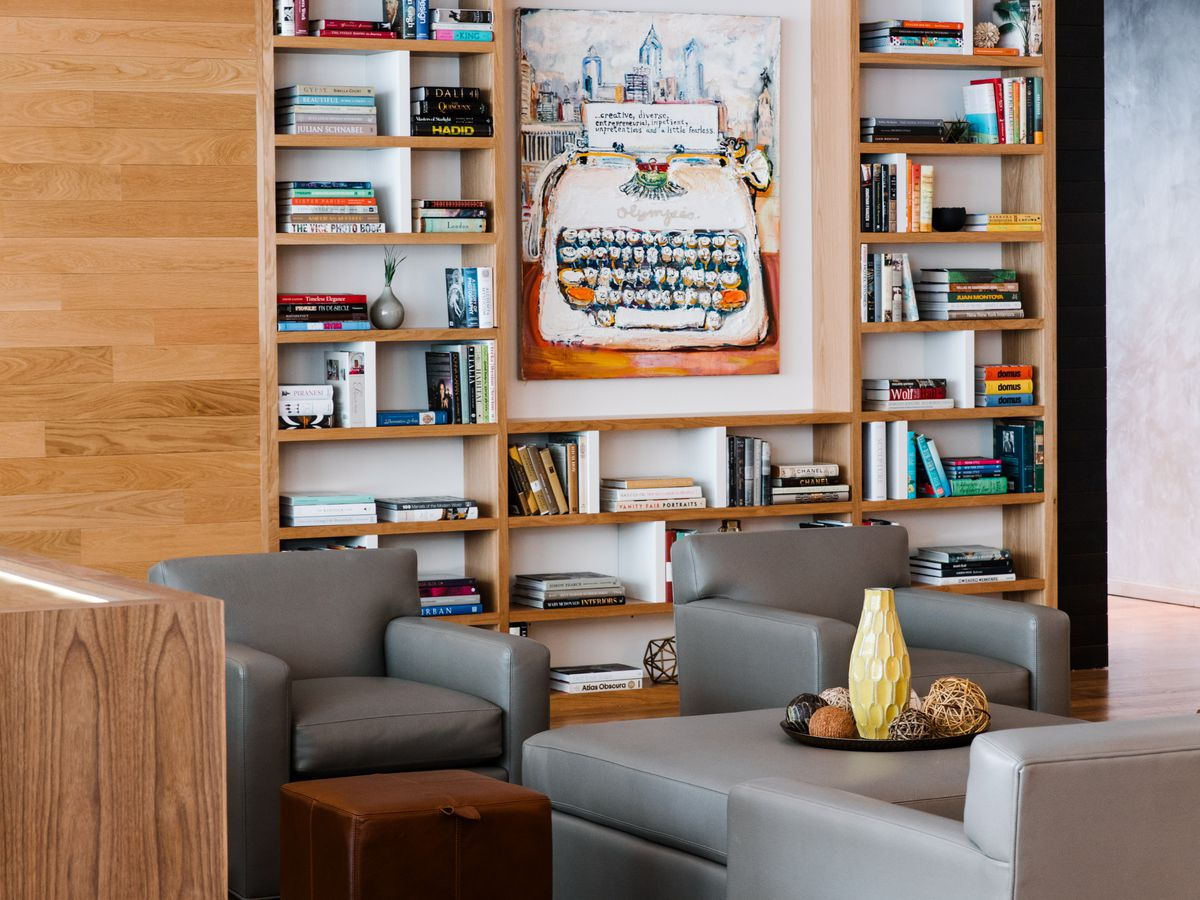 The interior of a room at the Study at University City. There are couches, tables, and bookshelves full of books and objects.