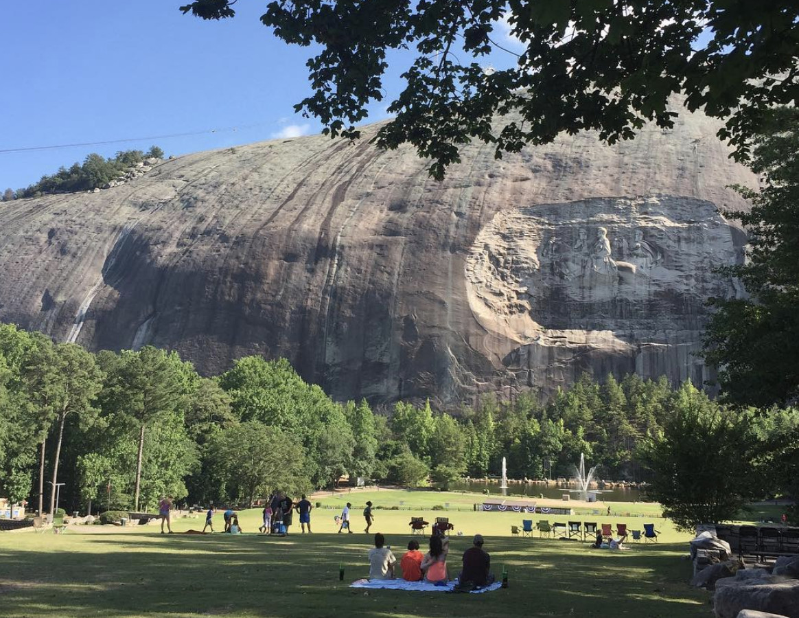 People sit on a lawn with trees. In the distance is a large stone mountain.
