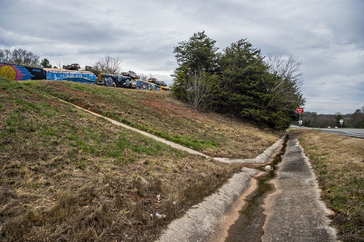 A ditch leading up to painted school buses.