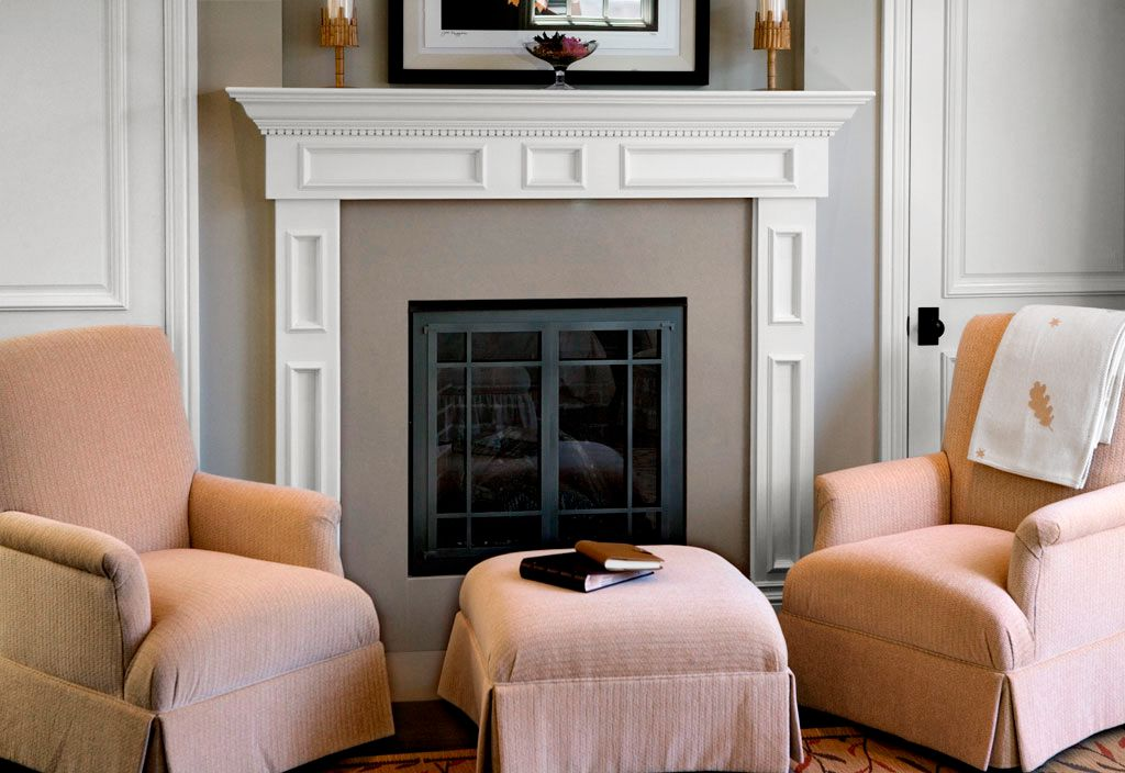 Two armchairs in front of a fireplace in the living room.