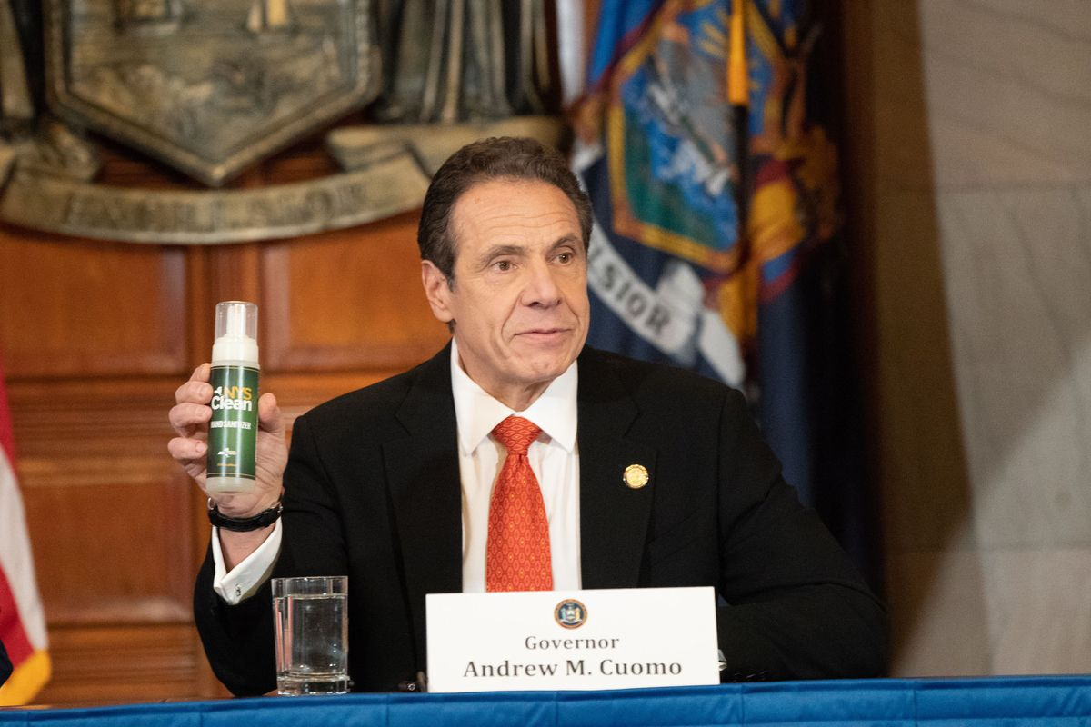 Gov. Andrew Cuomo holds up a bottle of free New York State hand sanitizer.