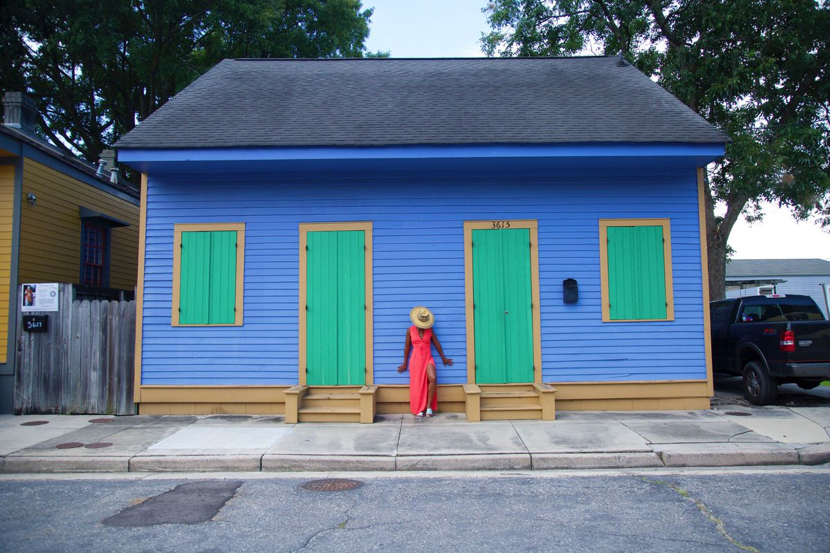 A woman in a red dress strikes a pose against a blue and green house.