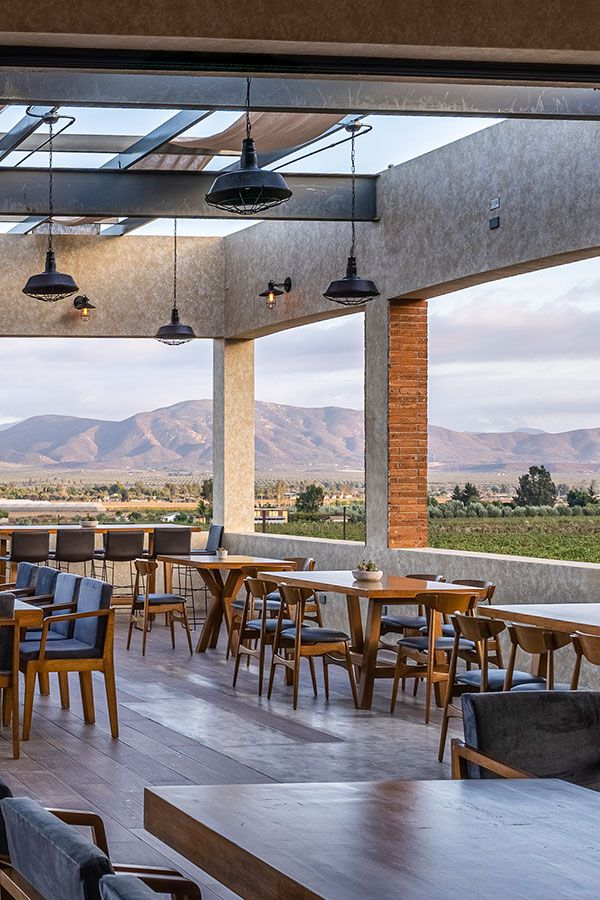 A covered stone patio, surrounded by low walls and looking out on green pastures and mountains in the distance. There are empty wood tables with midcentury wood and leather chairs and higher bar seating along one wall