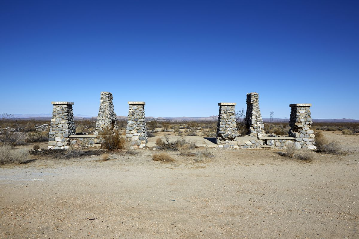 A group of 6 stone structures surrounded by desert.