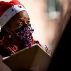Yvonne Ryans checks in an arriving car as she help distribute foodat Calvary Baptist Church in Salt Lake City on Saturday, Dec. 19, 2020.