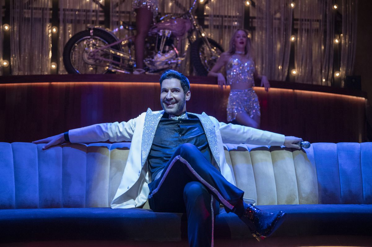 Tom Ellis as Lucifer sits smugly on a couch under blue light in season 6 of Lucifer