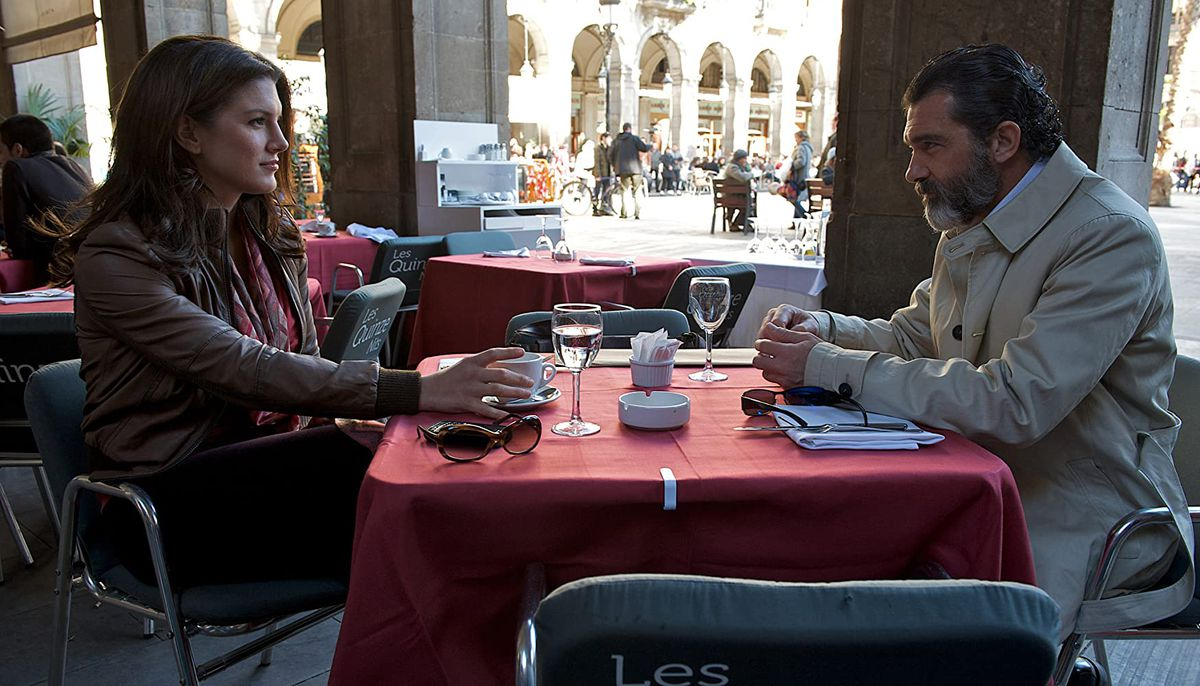Antonio Banderas and Gina Carano share a look over a cafe table in a screenshot from Haywire