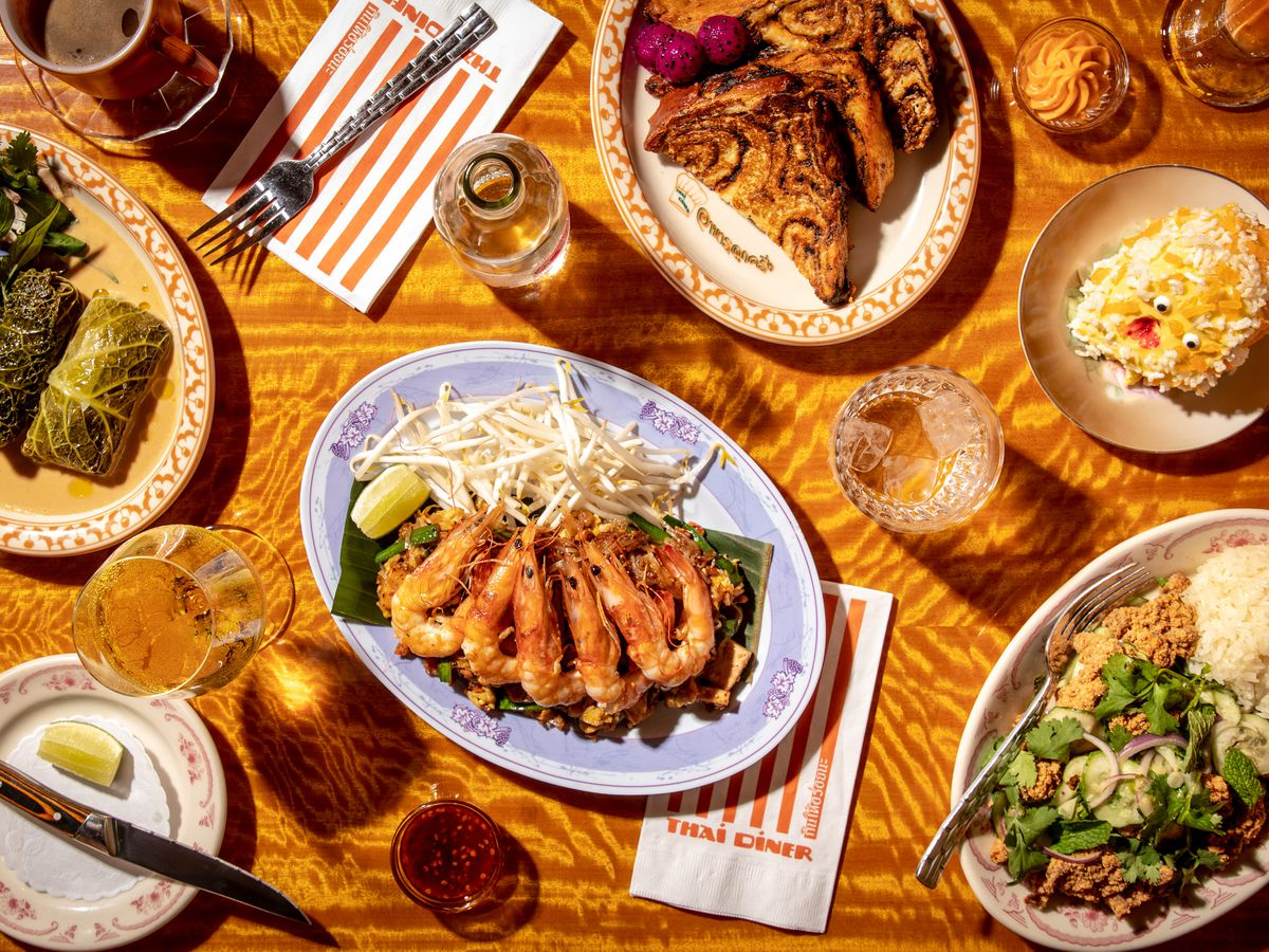 A spread of dishes shot from overhead, including verdant cabbage rolls, phat Thai noodles with pink head-on shrimp, fried chicken larb, and Thai tea pain perdu made from marbled babka