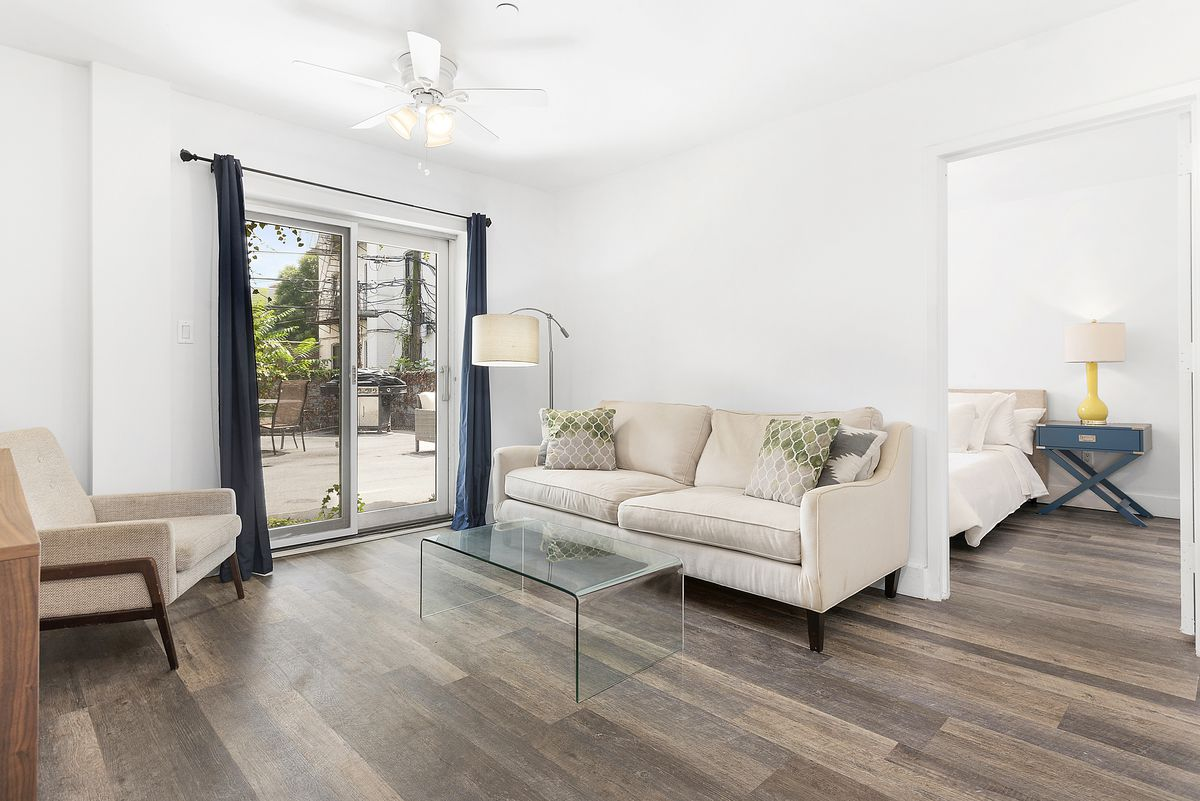 A living room area with hardwood floors, white walls, a beige couch, and a glass door that leads to a balcony.