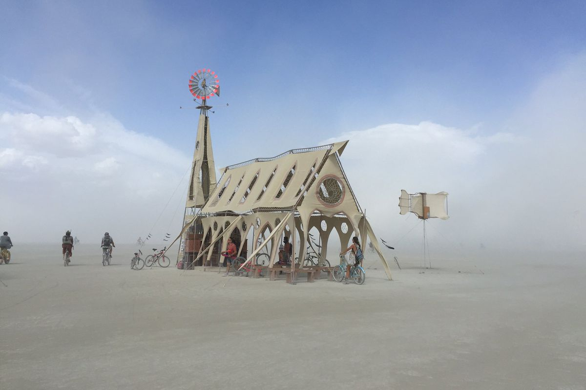 A wooden makeshift church temple with a red windmill on top in the dusty desert.