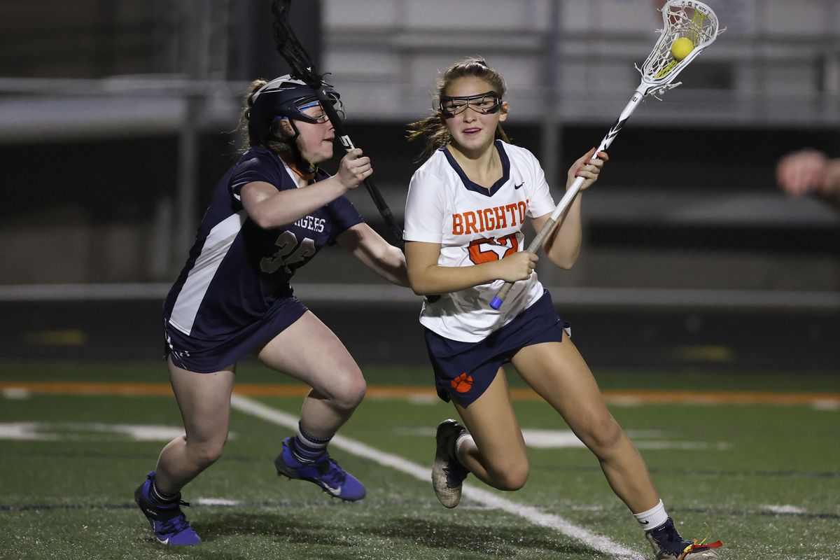 Brighton's Zoe Heffernan cradles the ball as Corner Canyon's Kenzie Zimmerman guards her during a girls lacrosse game at Brighton High School in Cottonwood Heights on Friday, March 19, 2021. Brighton won 16-6.