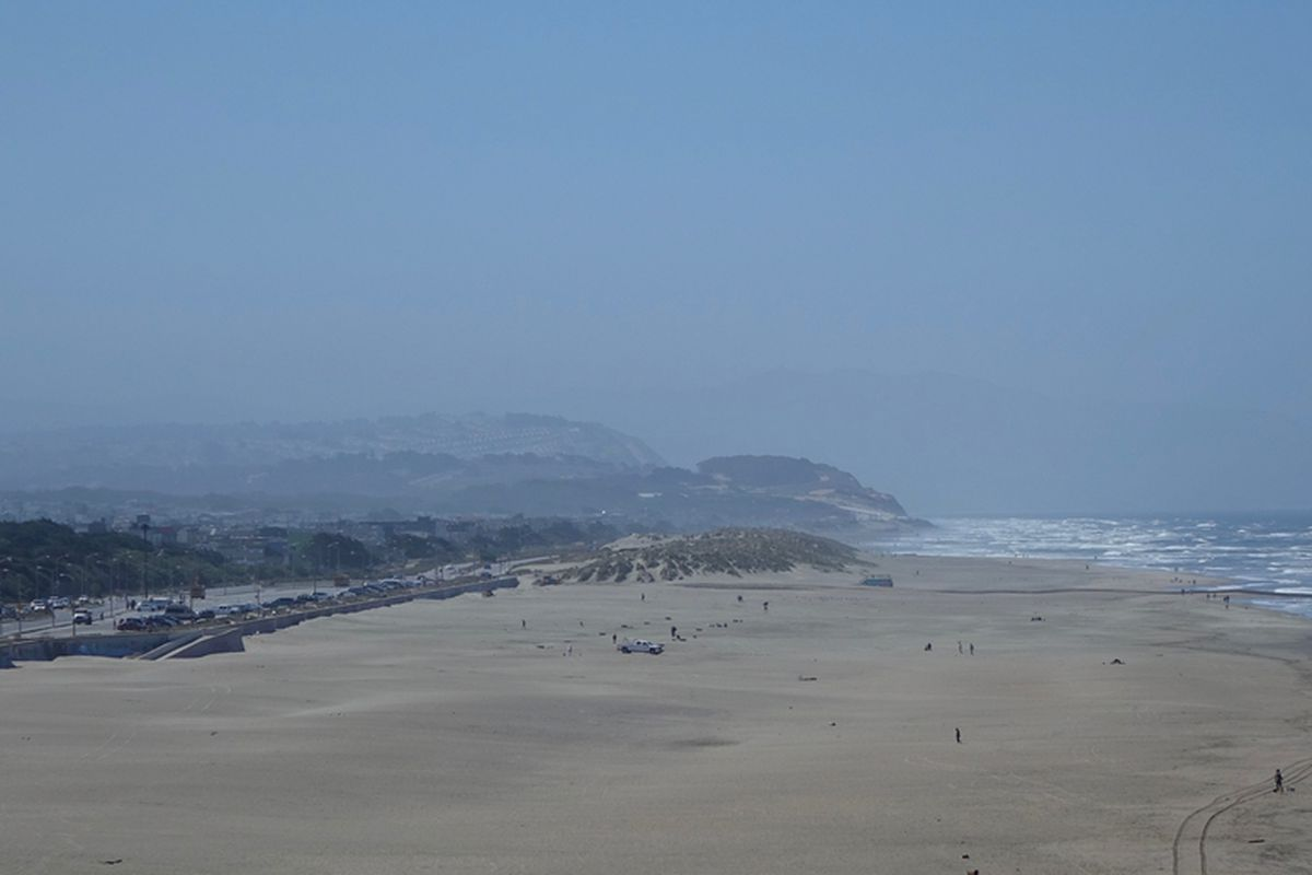 A photo of Ocean Beach with fog rolling in, with the Great Highway visible in the distance.