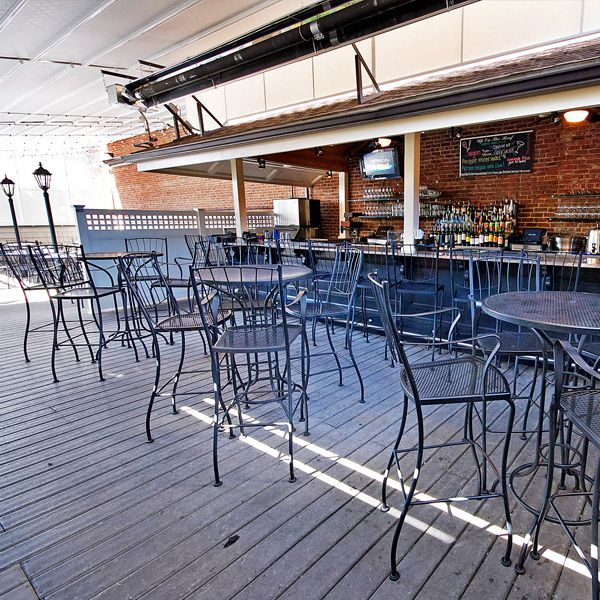 A restaurant's covered roof deck has black metal tables and chairs, a brick wall, and a full bar.