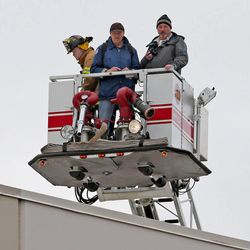 Investigators look down on the remains of a helicopter that crashed onto an empty building Tuesday afternoon, killing two men on board, Wednesday, Dec. 3, 2014, in North Salt Lake.