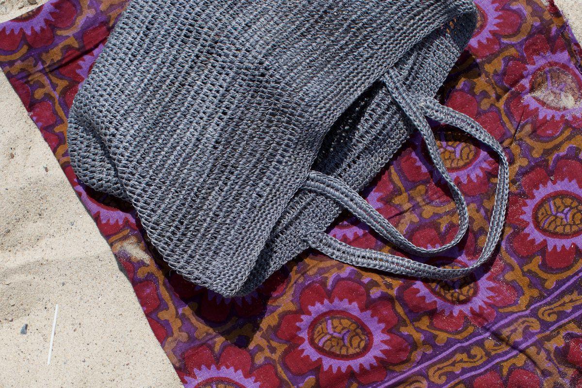 A grey woven bag on purple blanket