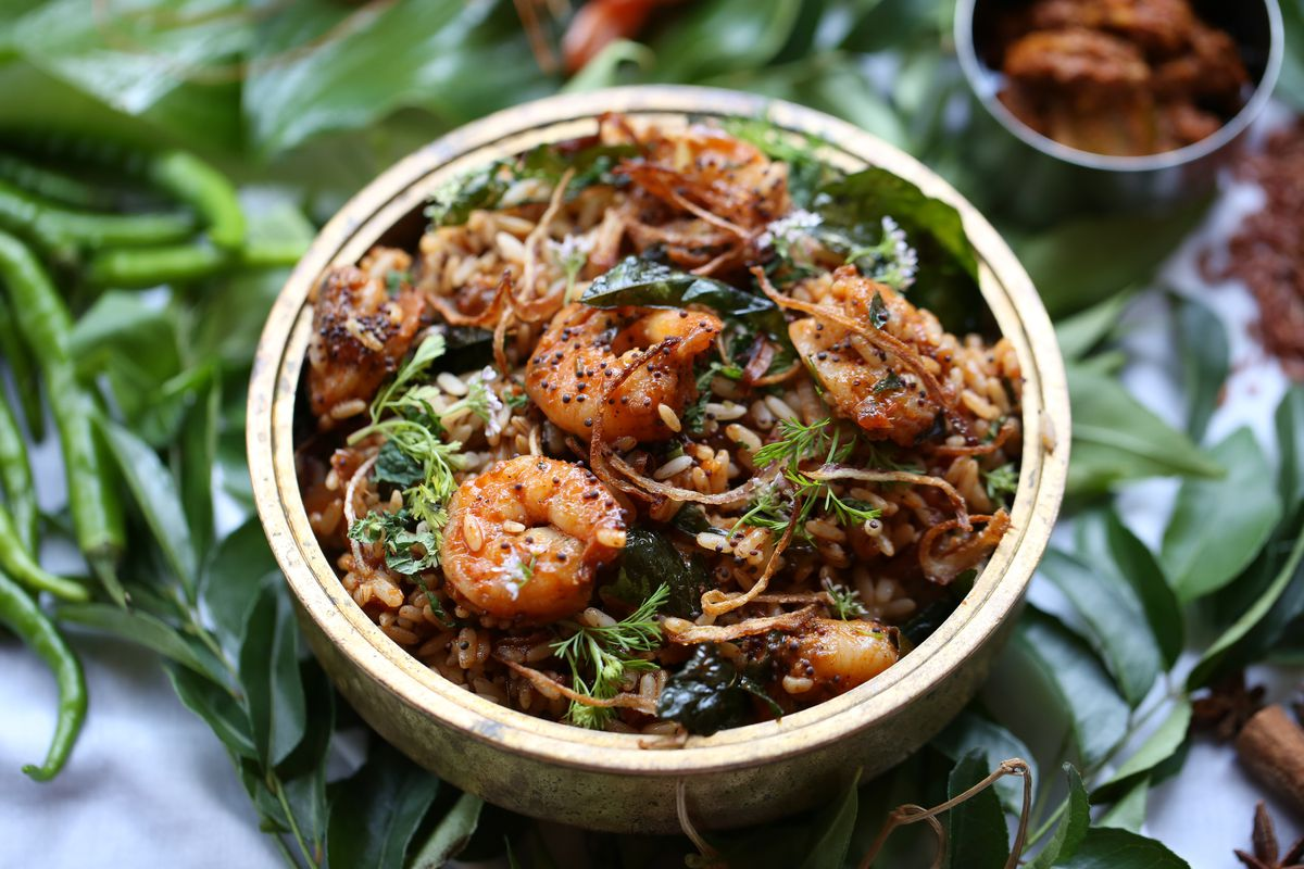 Shrimp biryani and rice in a thick stone bowl over a background of herbs and plants