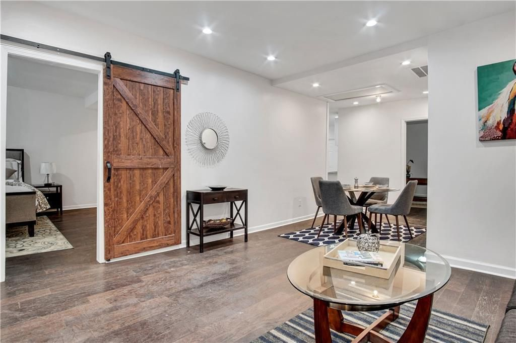 Open living space with coffee table in front, kitchen table and chairs in the back, and an open barn door leading into the bedroom.