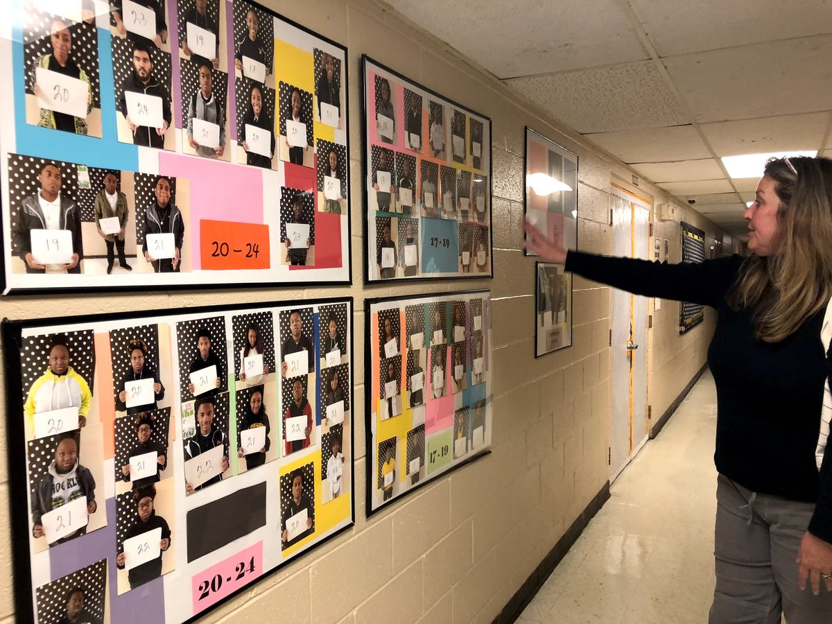 ACT prep teacher Patricia Ange shows off a wall of students with high scores on the college readiness test.