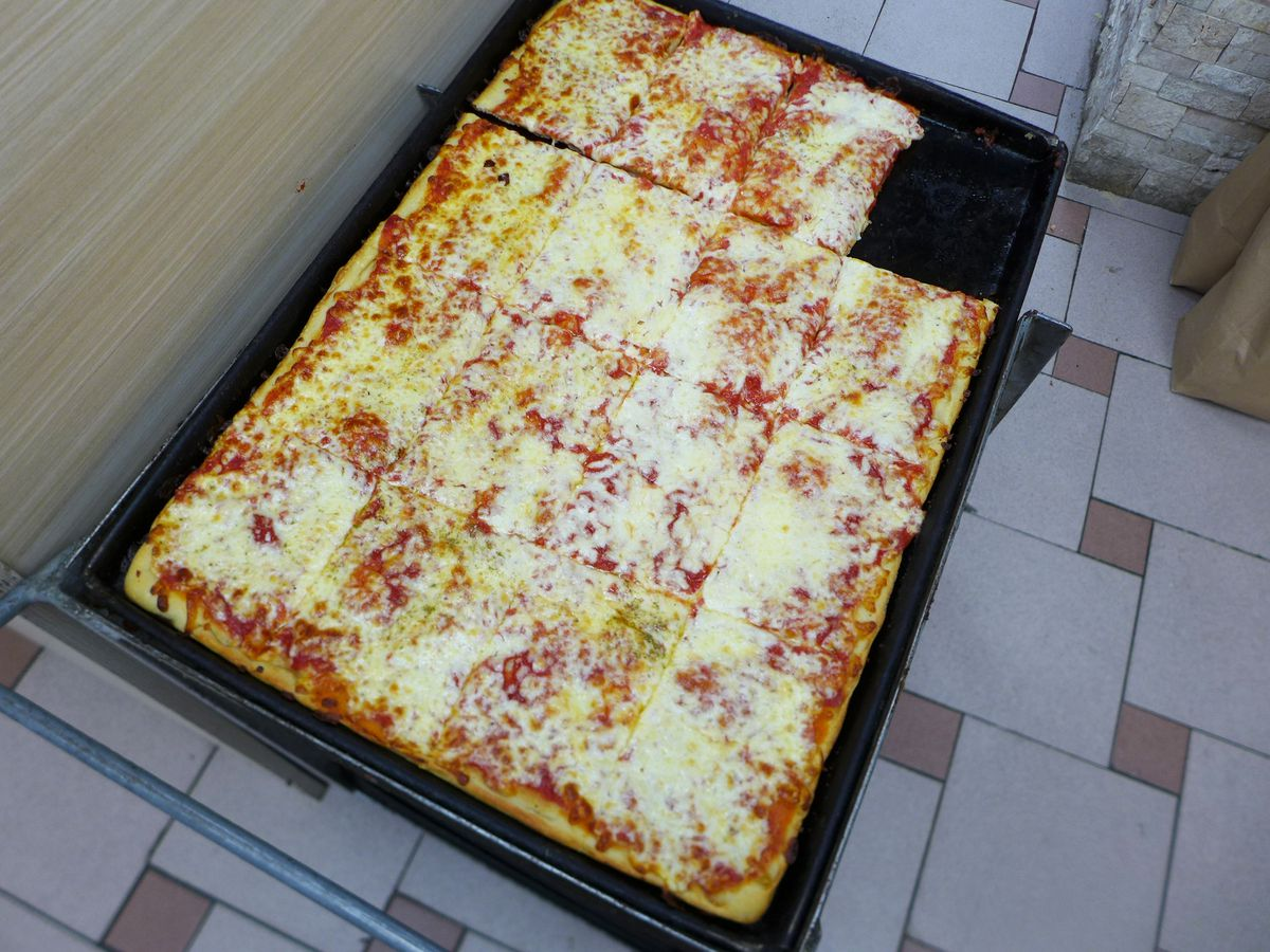A blacked rectangular pie with cheesy slices of pizza, with one in the corner missing.