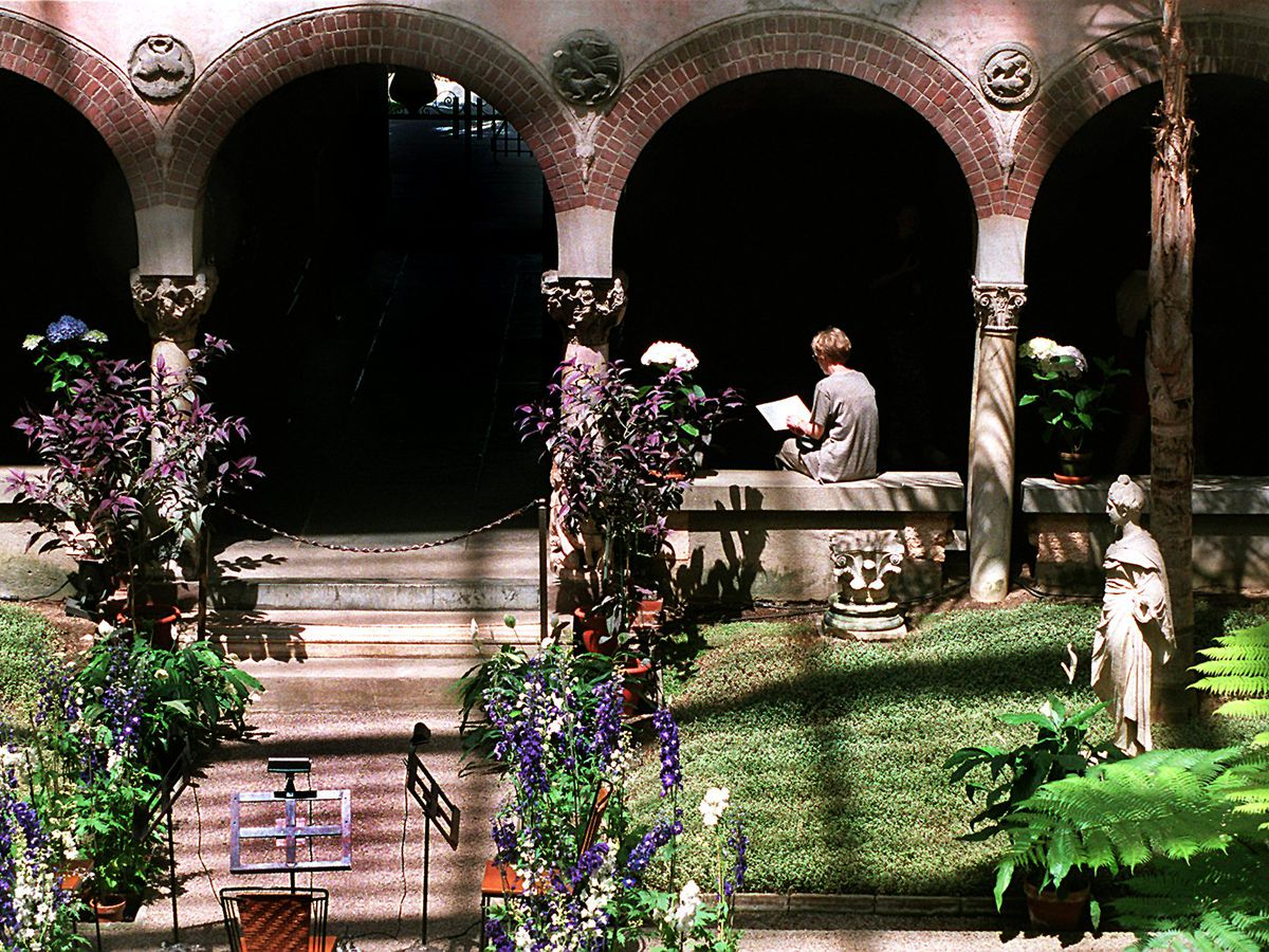 An interior garden with lush trees and grass, and an arched outside hallway with someone reading on one of the hall's walls.