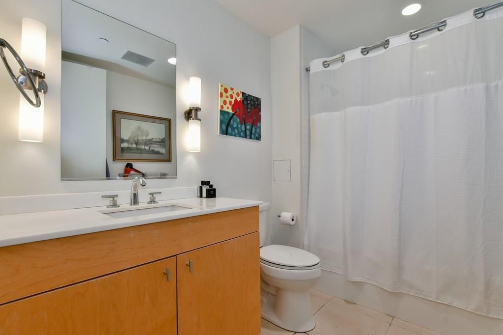 A bathroom with a long counter next to a toilet next to a tub with the curtain pulled closed.