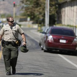 A police official carries a helmet as he walks past the Maplewood Apartments after a shooting in Lakeside, Calif., Tuesday, Sept. 25, 2012. The San Diego County sheriff's Capt. Duncan Fraser said two deputies and a suspect have been shot while the deputies were trying to contact a child abuse suspect at the suburban apartment complex.