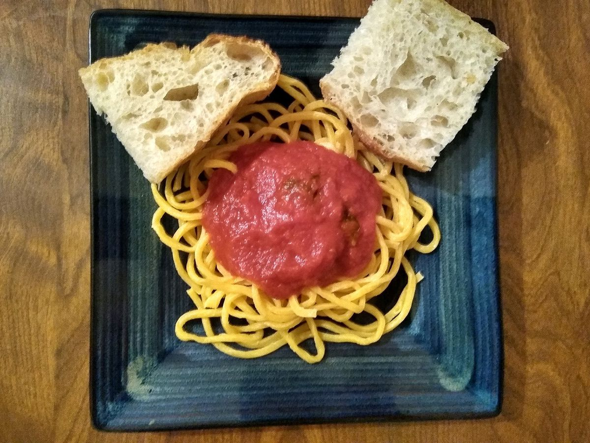 A portion of yellow spaghetti noodles topped with a red sauce and two slices of bread sit on a blue square plate on a wooden table
