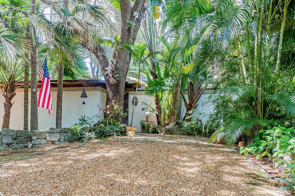 A lush backyard view of a bungalow in Coconut Grove with towering trees and oaks amid a green atmosphere.