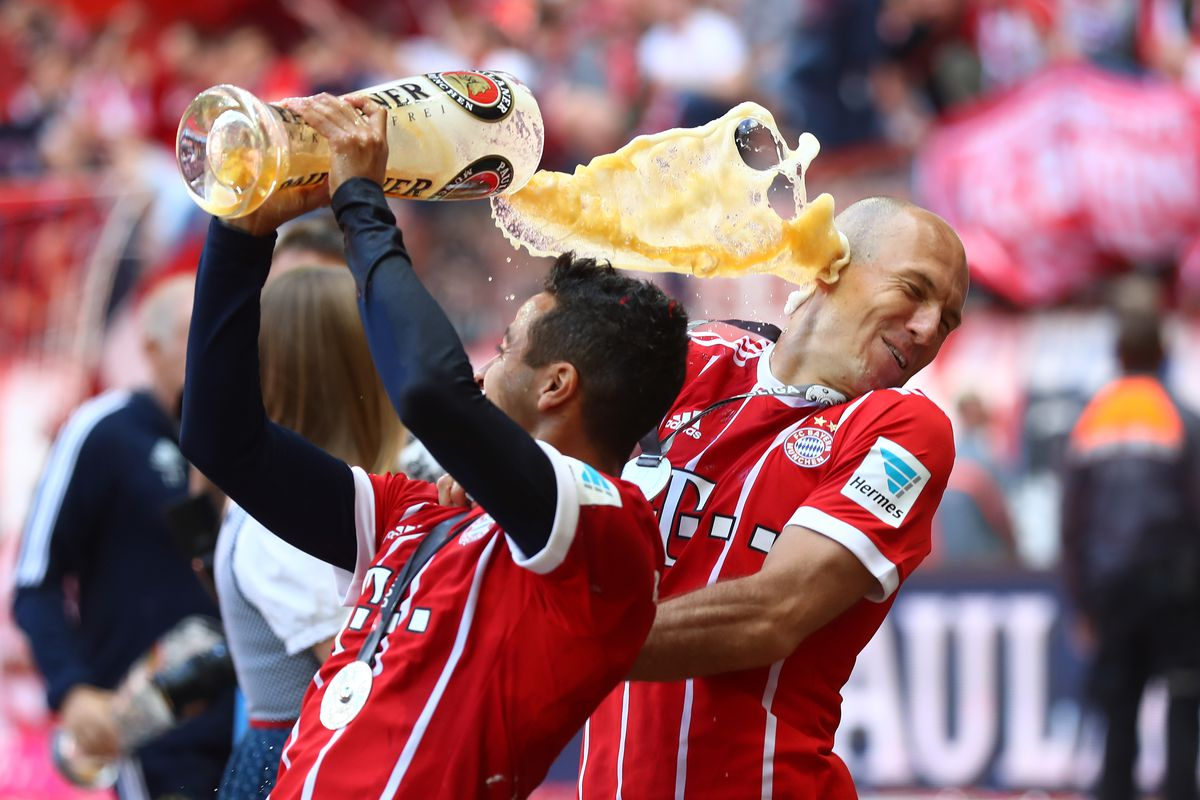 MUNICH, GERMANY - MAY 20: Arjen Robben (R) of Bayern Muenchen is showered in beer by teammate Thiago of Bayern Muenchen following the Bundesliga match between Bayern Muenchen and SC Freiburg at Allianz Arena on May 20, 2017 in Munich, Germany.