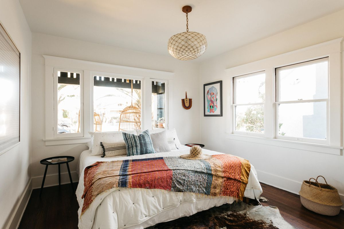 Bedroom with large windows on two walls.