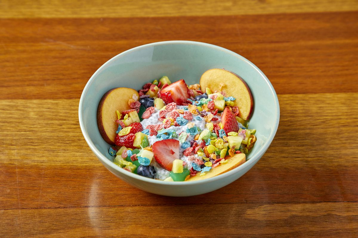 A colorful bowl of sweet pudding, fruit, jelly, and cereal