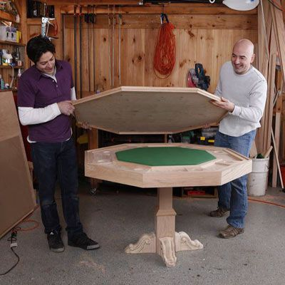 Two people placing a plywood lid over the felt table to assemble a DIY poker table.