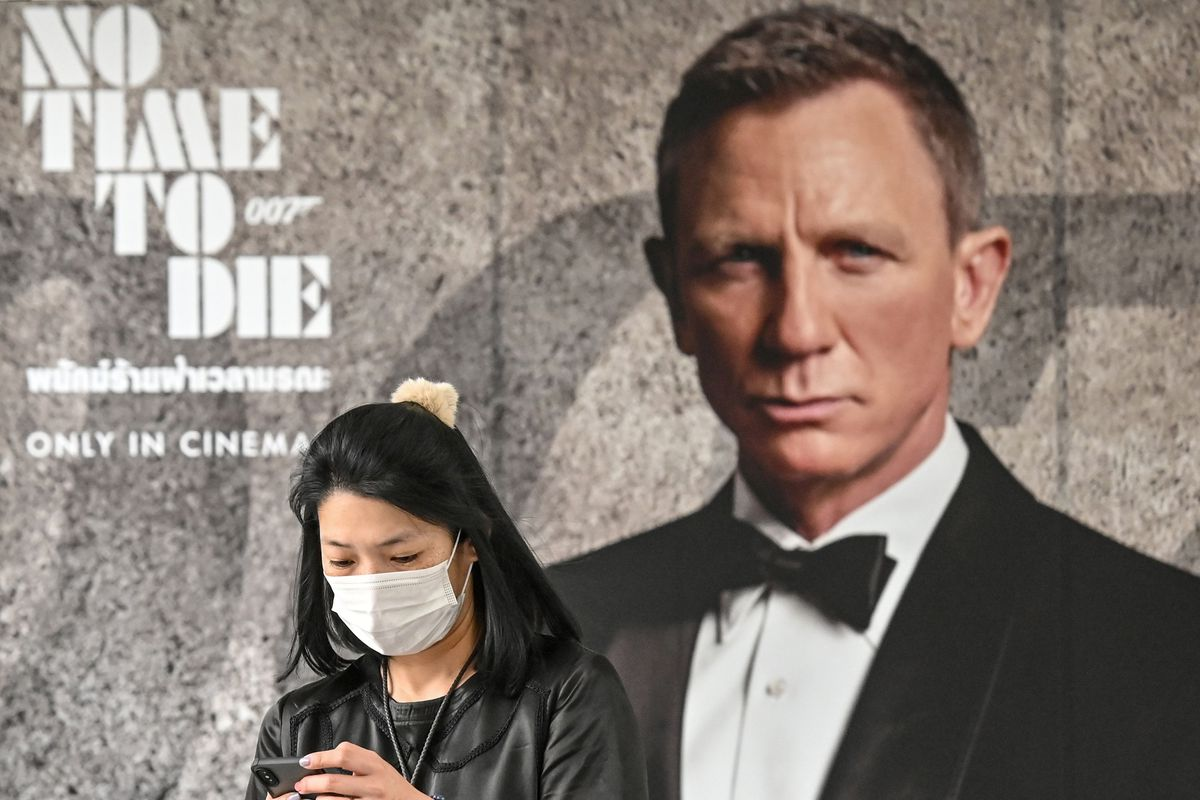 """A a woman wearing a facemask amid fears of the spread of the COVID-19 novel coronavirus walks past a poster for the new James Bond movie """"No Time to Die"""" in Bangkok. The movie's release has been delayed till November over fears the virus would limit its box-office appeal."""