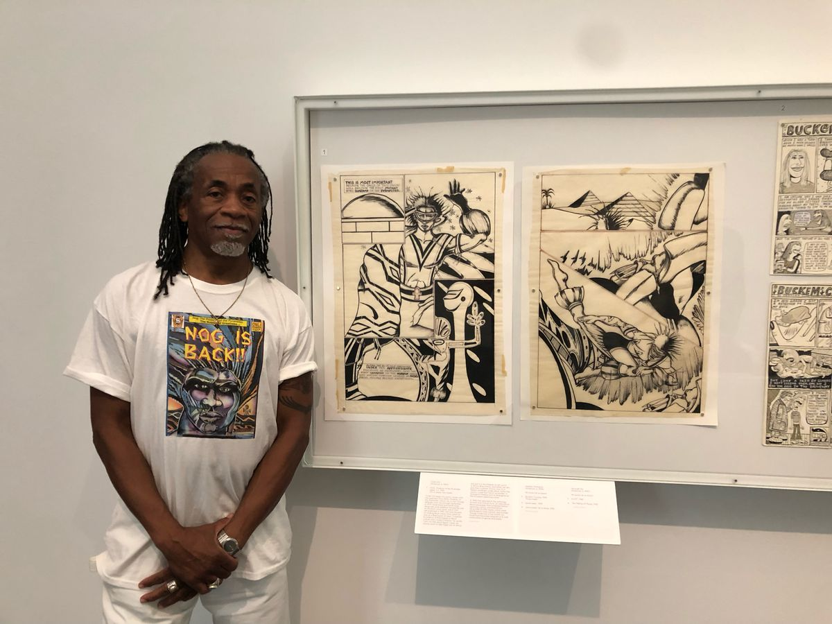 Turtel Onli next to his comic strip at the exhibition