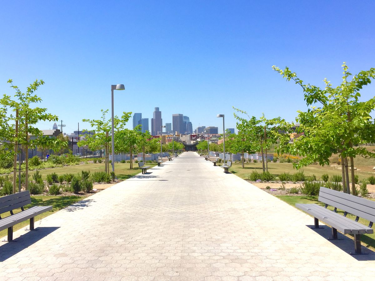 Park benches are on both sides of a wide path in Los Angeles State Historic Park. In the distance is a city skyline with tall buildings.