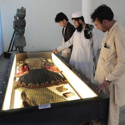In this Wednesday, Aug. 29, 2012 photo, visitors look at a traditional woman's dress displayed at the National Museum of Afghanistan in Kabul. Right  down to the power cuts that frequently plunge its artifacts into shadow, the National Museum of Afghanistan is a symbol of the country's recent hardships. Its building was shelled, looted and caught fire during the 1992s civil war. Taliban extremists later smashed many centuries- old statues.