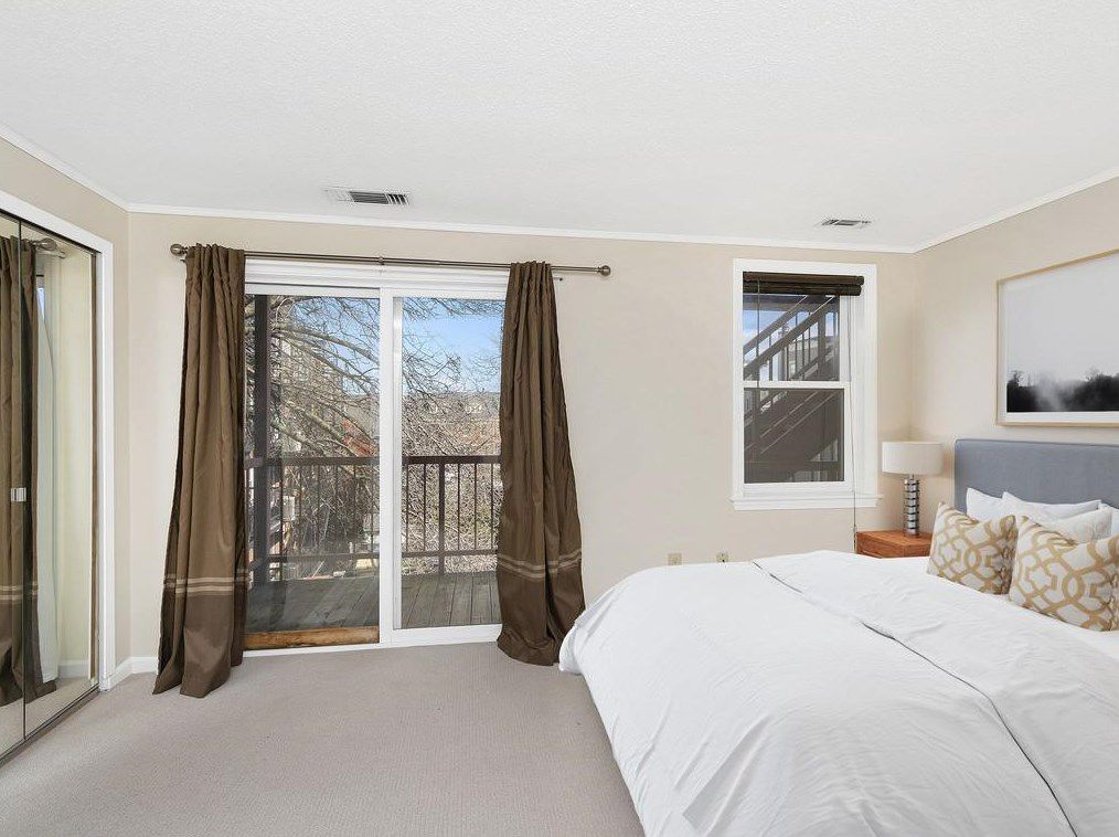 An airy bedroom with a bed and sliding glass doors leading to a small balcony.