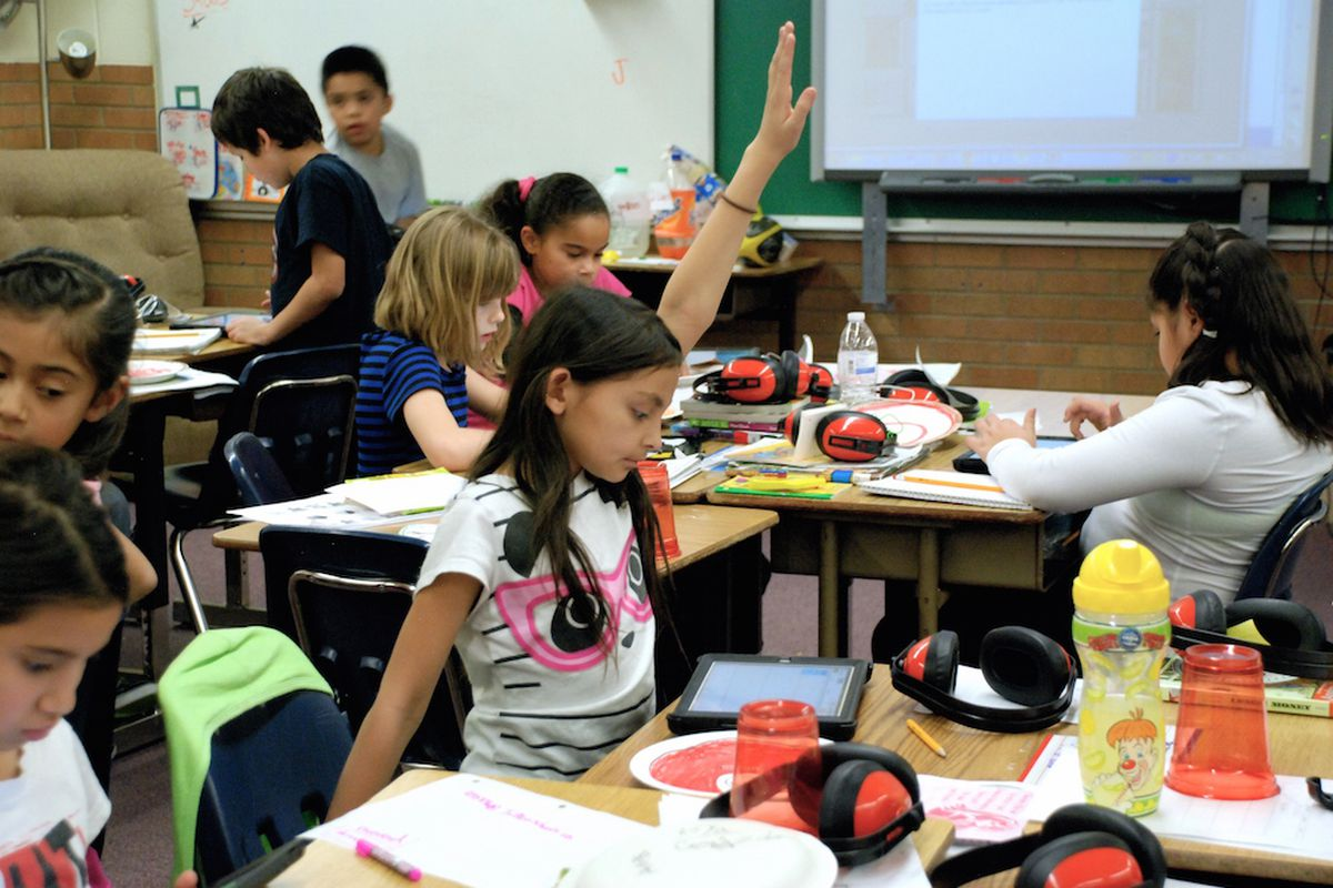 A student at Lumberg Elementary School in Edgewater raises her hand for assistance while students work on their iPads.