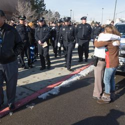Officers hug following funeral services for Unified police officer Doug Barney at the Maverik Center in West Valley City on Monday, Jan. 25, 2016.