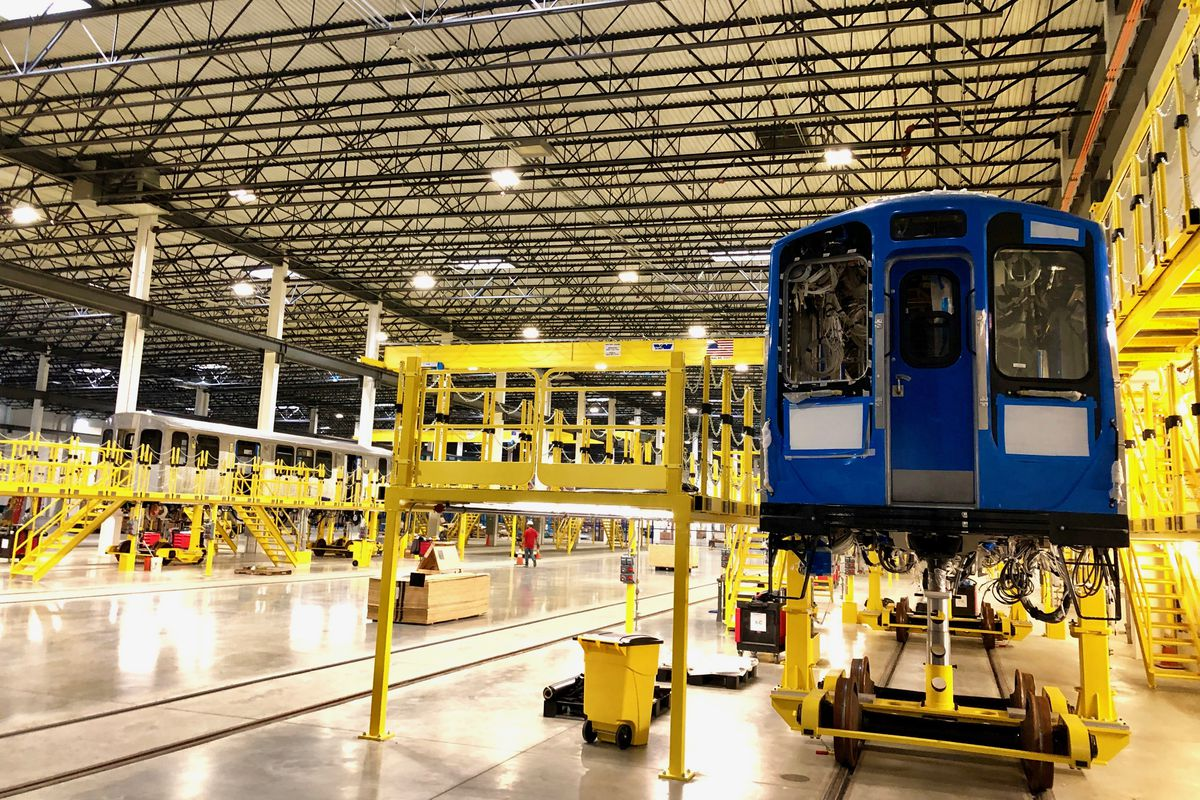 A blue CTA car under construction in a factory with yellow railings.