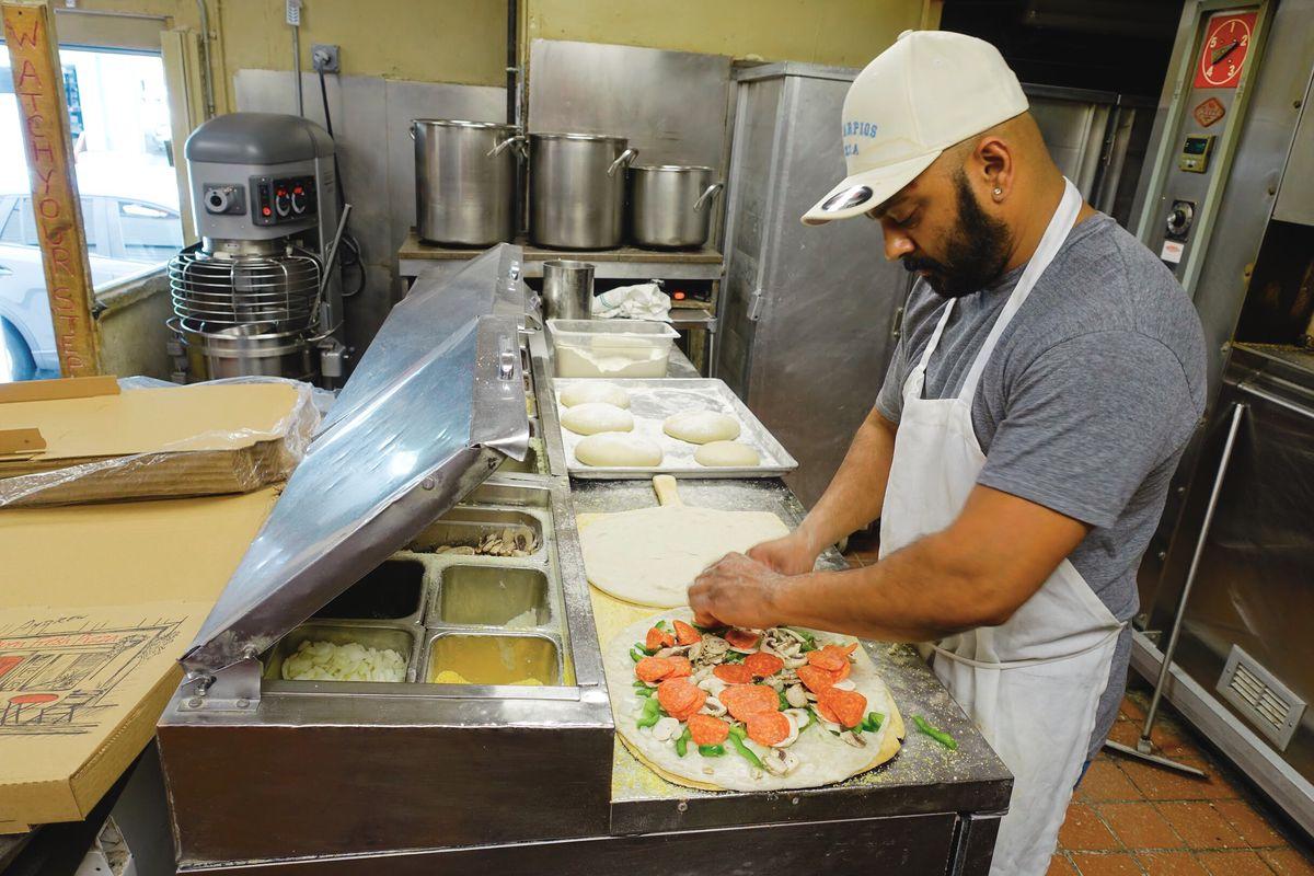 Longtime Santarpio's employee Richie Boodoosingh builds a pizza at Santarpio's