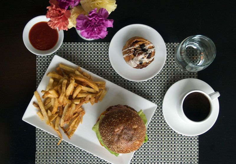 Overhead view of a dark table with coffee, a glass of water, flowers, a sandwich with fries, and more.