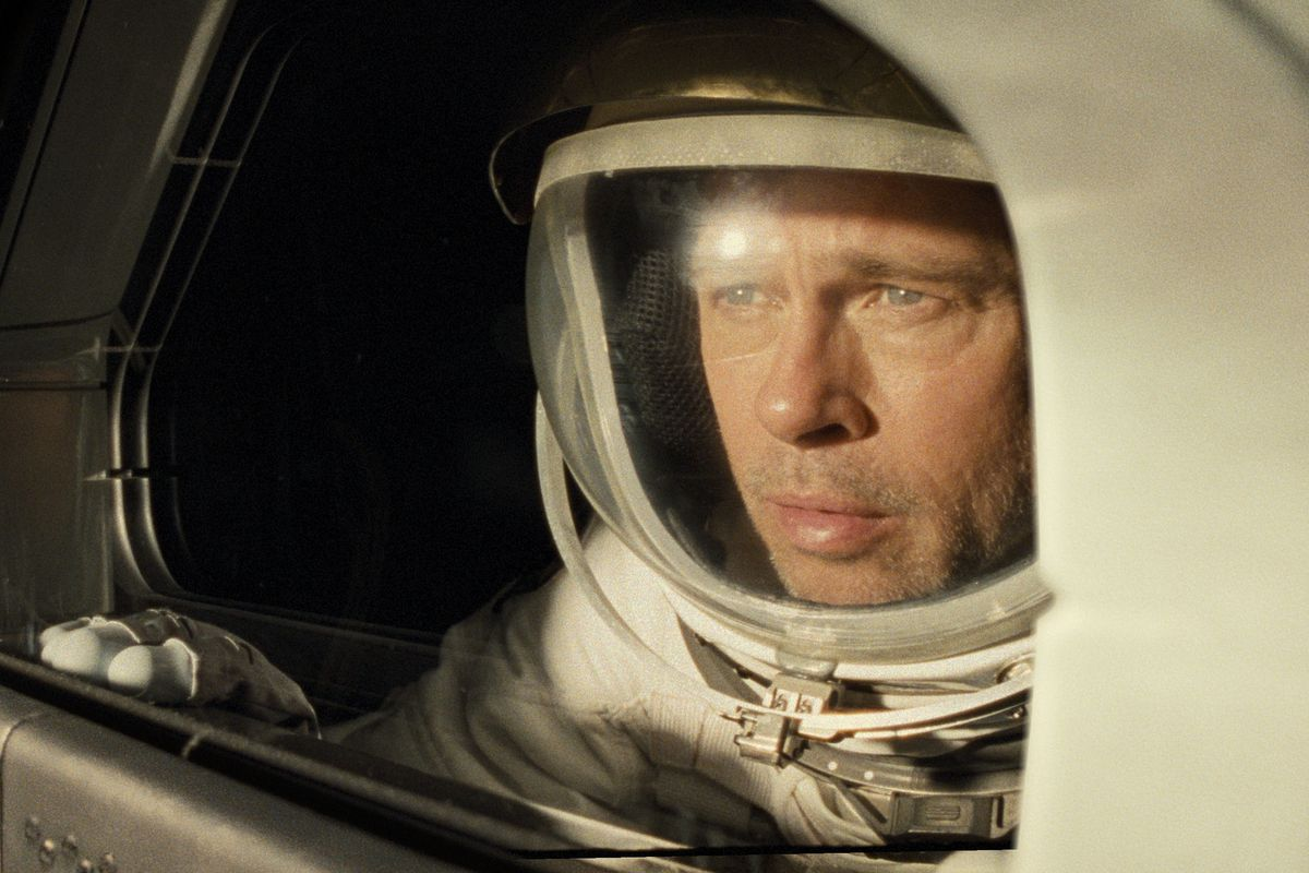 brad pitt's roy wears a space suit and watches out a window as his shuttle passes the sun