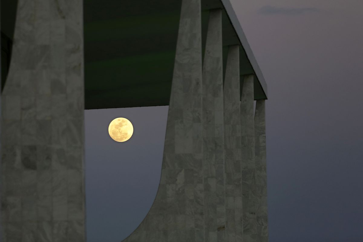 A full moon rises between the arches of the Planalto Presidential Palace amid the new coronavirus pandemic, in Brasilia, Brazil, Tuesday, Sept. 1, 2020.