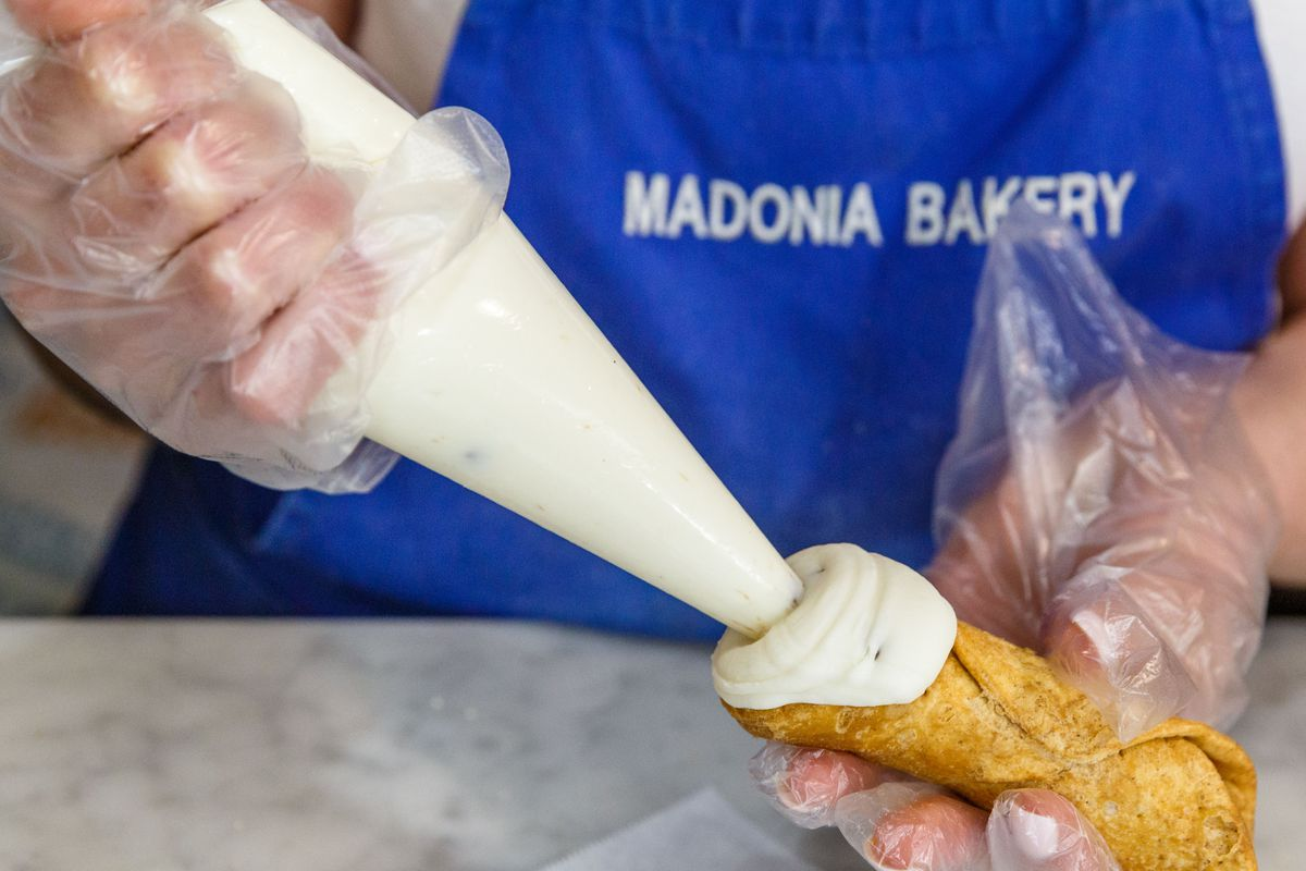 A cannoli being filled at Madonia Brothers Bakery